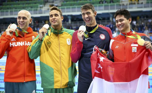 2016 Rio Olympics - Swimming - Victory Ceremony - Men's 100m Butterfly Victory Ceremony - Olympic Aquatics Stadium - Rio de Janeiro, Brazil - 12/08/2016. Gold medallist Joseph Schooling (SIN) of Singapore holds his national flag while posing with joint silver medallists Michael Phelps (USA) of USA, Chad Le Clos (RSA) of South Africa and Laszlo Cseh (HUN) of Hungary.   REUTERS/Michael Dalder  FOR EDITORIAL USE ONLY. NOT FOR SALE FOR MARKETING OR ADVERTISING CAMPAIGNS.