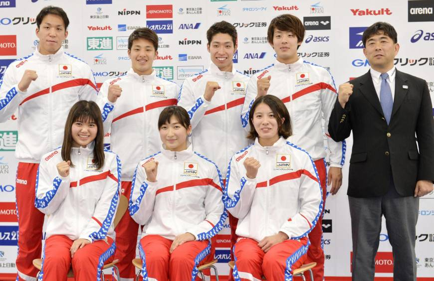 Seven members of Japan's national swimming team for the July 23-30 world championships and coach Norimasa Hirai (far right) pose for a photo on Monday. | KYODO
