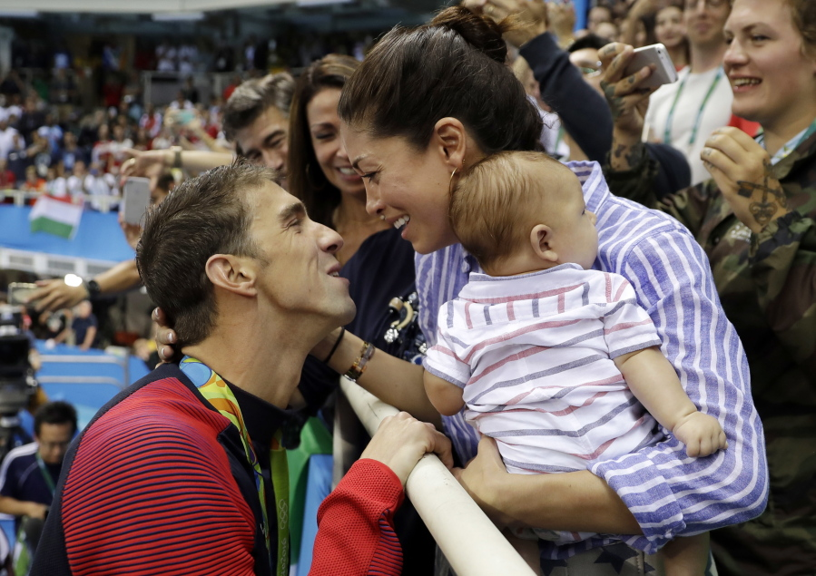 """Michael Phelps celebrates winning his gold medal in the men's 200-meter butterfly with his fiance Nicole Johnson and baby Boomer during the swimming competitions at the 2016 Summer Olympics in Rio de Janeiro, Brazil. Phelps says he has """"no desire"""" to return to competitive swimming, but he's eager to stay involved with the sport and cheer on those who follow in his enormous wake. (AP Photo/Matt Slocum, File)"""
